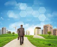 Businessman walks on road. Rear view. Buildings, Stock Photos