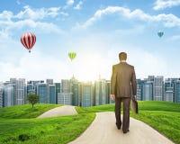 Businessman walks on road. Rear view. City skyline Stock Image