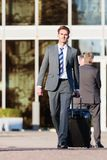 Businessman walks with a trolley bag. In the city Royalty Free Stock Photo