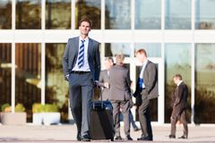 Businessman walks with a trolley bag. In the city Royalty Free Stock Images