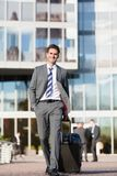 Businessman walks with a trolley bag. In the city Stock Images