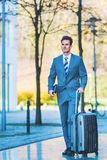 Businessman walks with a trolley bag in the city. Picture of a businessman who walks with a trolley bag in the city Royalty Free Stock Photography