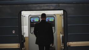 Businessman Walks Into A Underground Carriage. Slow motion back view shot of a businessman walks into a underground carriage and doors are closed stock footage