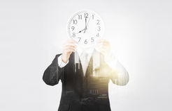 Businessman with wall clock. People, business and time concept - businessman covering his face behind wall clock over city with double exposure Royalty Free Stock Images
