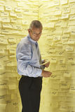 Businessman By Wall Covered In Sticky Notes. Businessman standing in front of wall covered in sticky notes Royalty Free Stock Image
