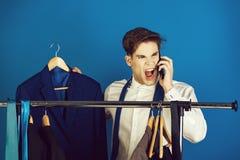 Businessman at wardrobe hanger with phone, shouting angry man stock photo