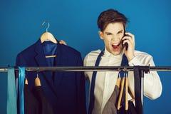 Businessman at wardrobe hanger with phone, shouting angry man royalty free stock photos