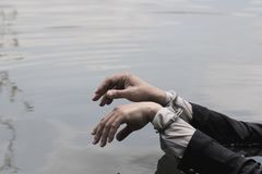 Businessman was arrested by handcuffs and drowning. Hand of a businessman handcuffed over water Stock Photo