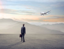 Businessman Watching an Airplane in a Wasteland Royalty Free Stock Images