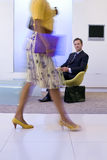 Businessman watching businesswoman walking in foyer, low section (blurred motion) Royalty Free Stock Image