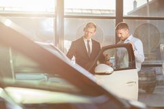 Businessman watching car in showroom Royalty Free Stock Image