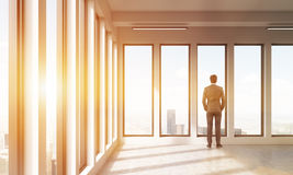 Businessman watching at city through panoramic windows. Adult man watches out of the window at big city at his feet. Concept of decision making. 3D render Stock Photos