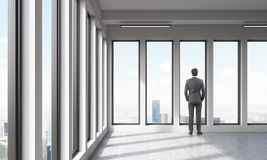 Businessman watching at city through panoramic windows. An adult watching at city out of large window in empty room. Concept of deep thinking. 3D render Royalty Free Stock Photography