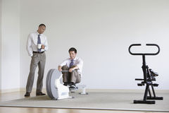Businessman Watching Colleague Use Rowing Machine Royalty Free Stock Photos