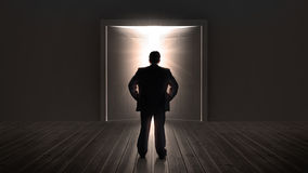 Businessman watching doors opening to a bright light. In the shadows Royalty Free Stock Photos