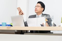 Businessman are working. Businessman is watching his cell phone while another hand is holding the report royalty free stock image