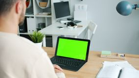 Businessman watching laptop with chroma key green screen in office at desk stock video footage