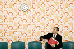 Businessman Watching the Time. Businessman checking the time in a waiting room with a funky wallpaper Stock Image