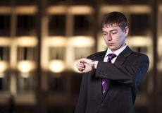 Businessman watching time at night city Stock Images