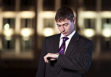 Businessman watching time at night city Stock Photo