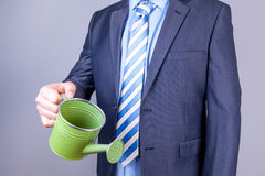 Businessman watering can Stock Image