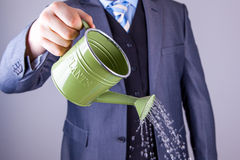 Businessman watering can Stock Photo