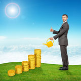 Businessman watering coins and showing ok Royalty Free Stock Photo