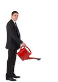 Businessman watering with red can and smiling at camera Royalty Free Stock Photo