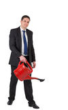 Businessman watering with red can and smiling at camera Royalty Free Stock Images