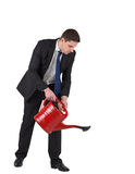 Businessman watering with red can Stock Images