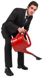 Businessman watering with red can Stock Photo