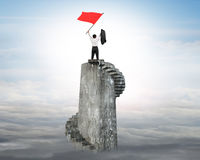 Businessman waving red flag on top of tower Stock Image