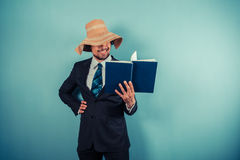 Businessman wearing beach hat is reading Stock Images