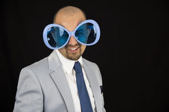 Businessman wearing big funky blue glasses Royalty Free Stock Photography