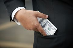 Businessman wearing a black suit. Hold a dollar bill. Put in a pocket The bracelets of the business.using as background business c. Oncept with copy space for Royalty Free Stock Photos