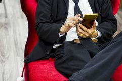 Businessman wearing a black suit sitting on a red velvet chair, Touch screen smartphone, During break, relax, wait for meeting royalty free stock photography