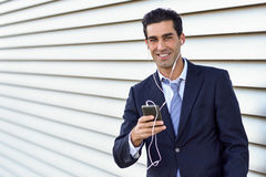 Businessman wearing blue suit and tie using a smartphone. Stock Image
