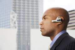 A businessman wearing a bluetooth headset Royalty Free Stock Images