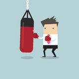 Businessman wearing boxing gloves and punching the punch bag Royalty Free Stock Image