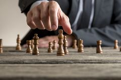 Businessman wearing business suit playing a game of chess. On an old wooden table in a close up view of his hand reaching black king piece Royalty Free Stock Photography