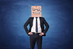 Businessman is wearing cardboard box with drawn angry face Royalty Free Stock Images