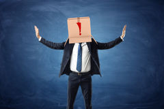 Businessman wearing cardboard box with drawn exclamation point on his head. Royalty Free Stock Image