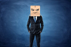 Businessman wearing cardboard box with drawn frowning face on his head Stock Photo