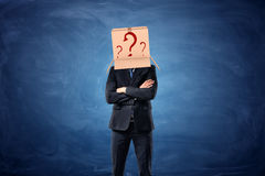 Businessman is wearing cardboard box with drawn question marks on his head Stock Image