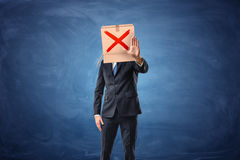 Businessman is wearing cardboard box with drawn red cross sign Royalty Free Stock Photos