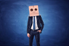 Businessman wearing cardboard box with drawn smiling face on his head on blue background Stock Image