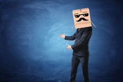 Businessman wearing cardboard box with drawn sun glasses and moustache on his head