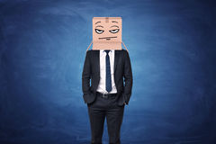 Businessman wearing cardboard box with drawn thoughtful face on his head Royalty Free Stock Photos