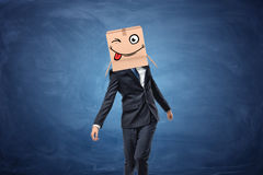Businessman wearing cardboard box with drawn winking face on his head Stock Image