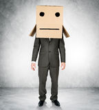 Businessman wearing carton box with drawn emotions Royalty Free Stock Image